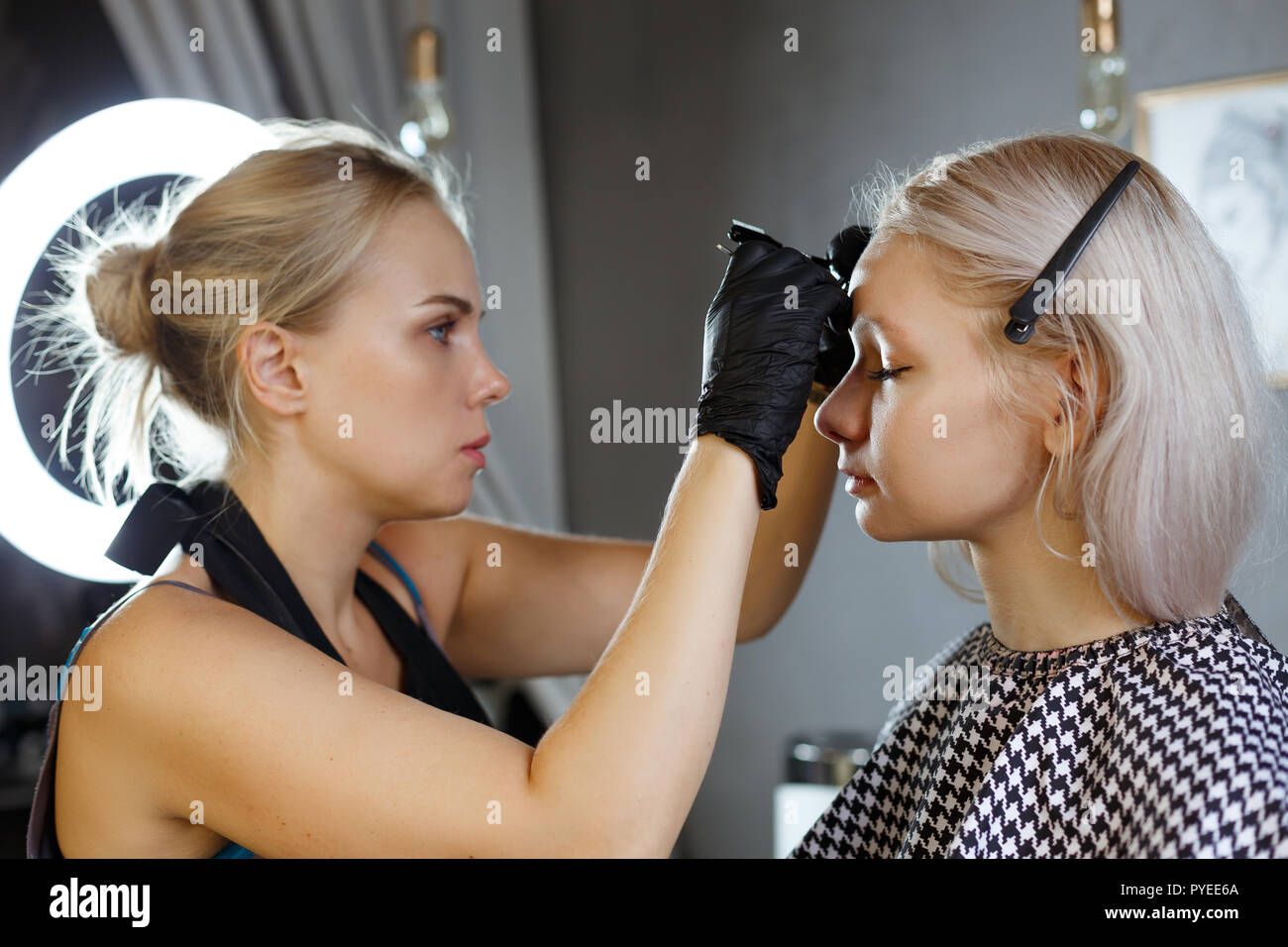 Beautiful young girl got correction of eyebrows in a beauty salon - Stock Image
