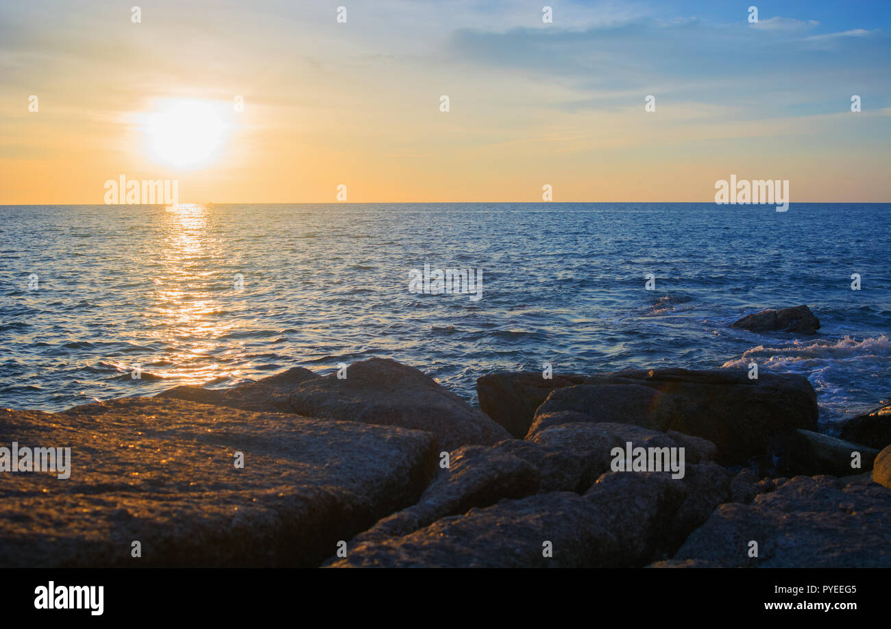 Rocky seashore and sunset over the sea Stock Photo