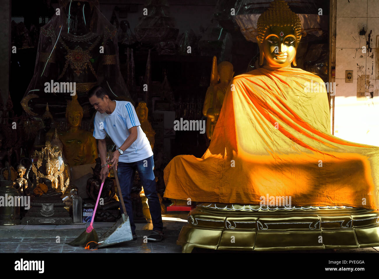 An employee of a shop selling Buddhist devotional objects in Bamrung Muang Rd., Bangkok, Thailand, sweeping the footpath in front of his shop - Stock Image