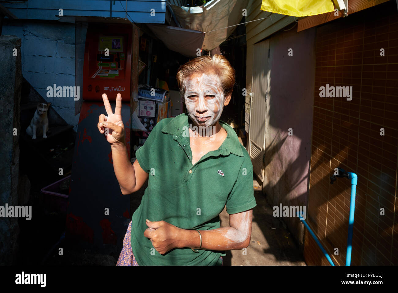 The ubiquitous V sign, performed by a Thai woman in a lower end neighbourhood in Bangkok, Thailand, her face covered in talcum powder to keep cool - Stock Image