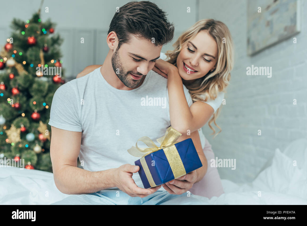 beautiful young woman presenting christmas gift to boyfriend in bed ...