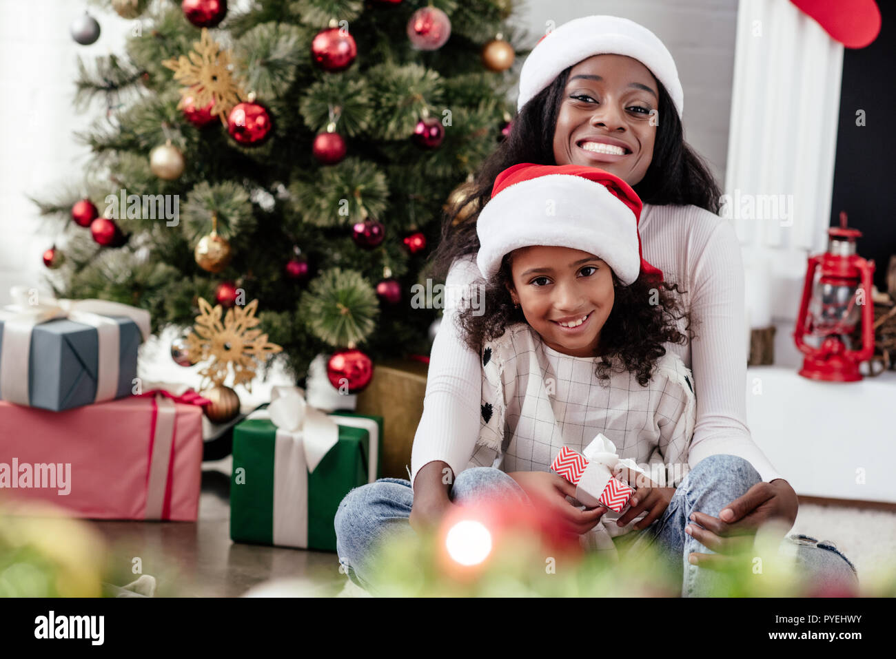 happy african american woman and daughter with gift in santa claus hats at home, newy year and christmas concept - Stock Image