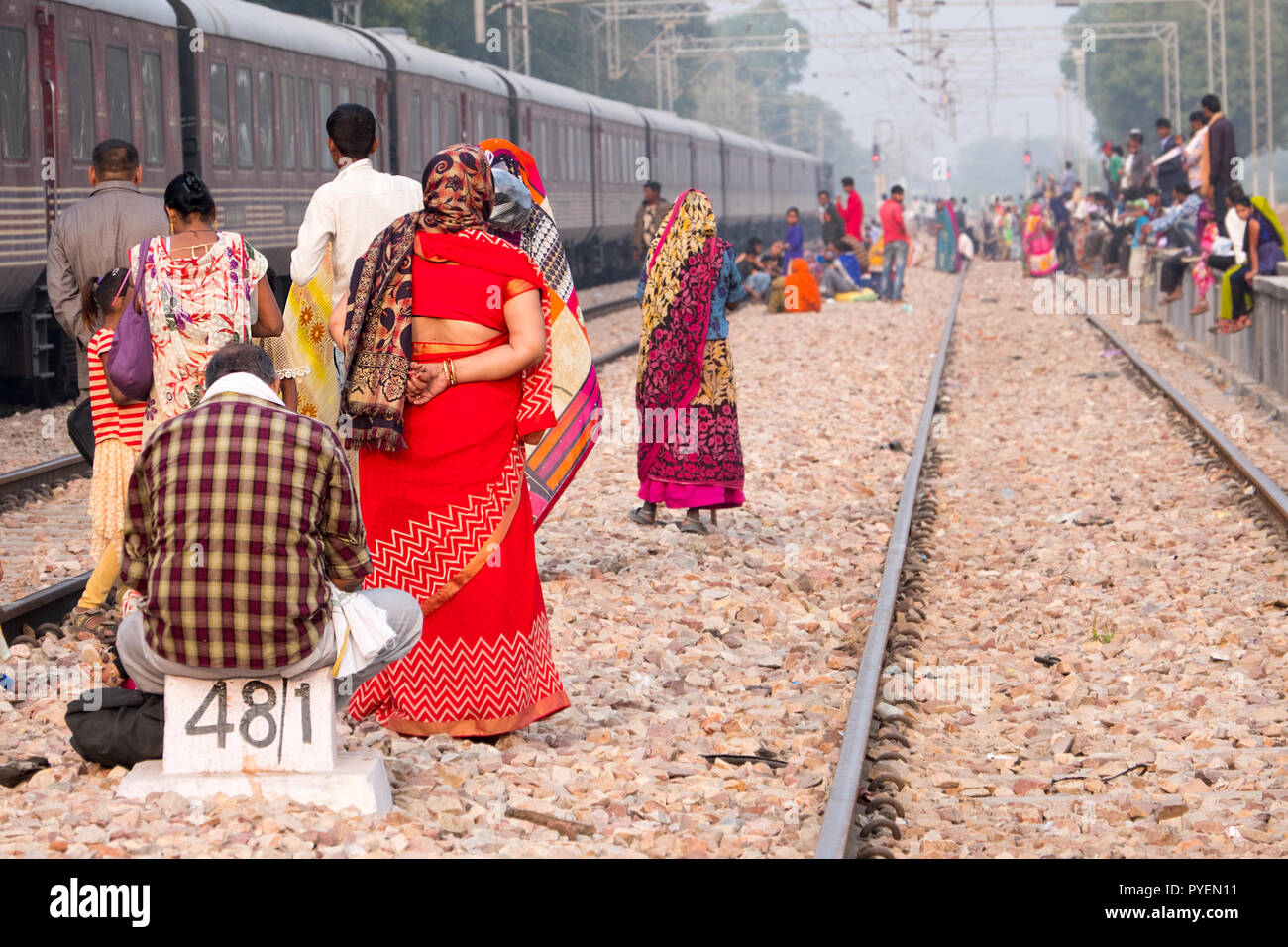 Indian passengers waiting on the rail tracks for a train to arrive, India - Stock Image