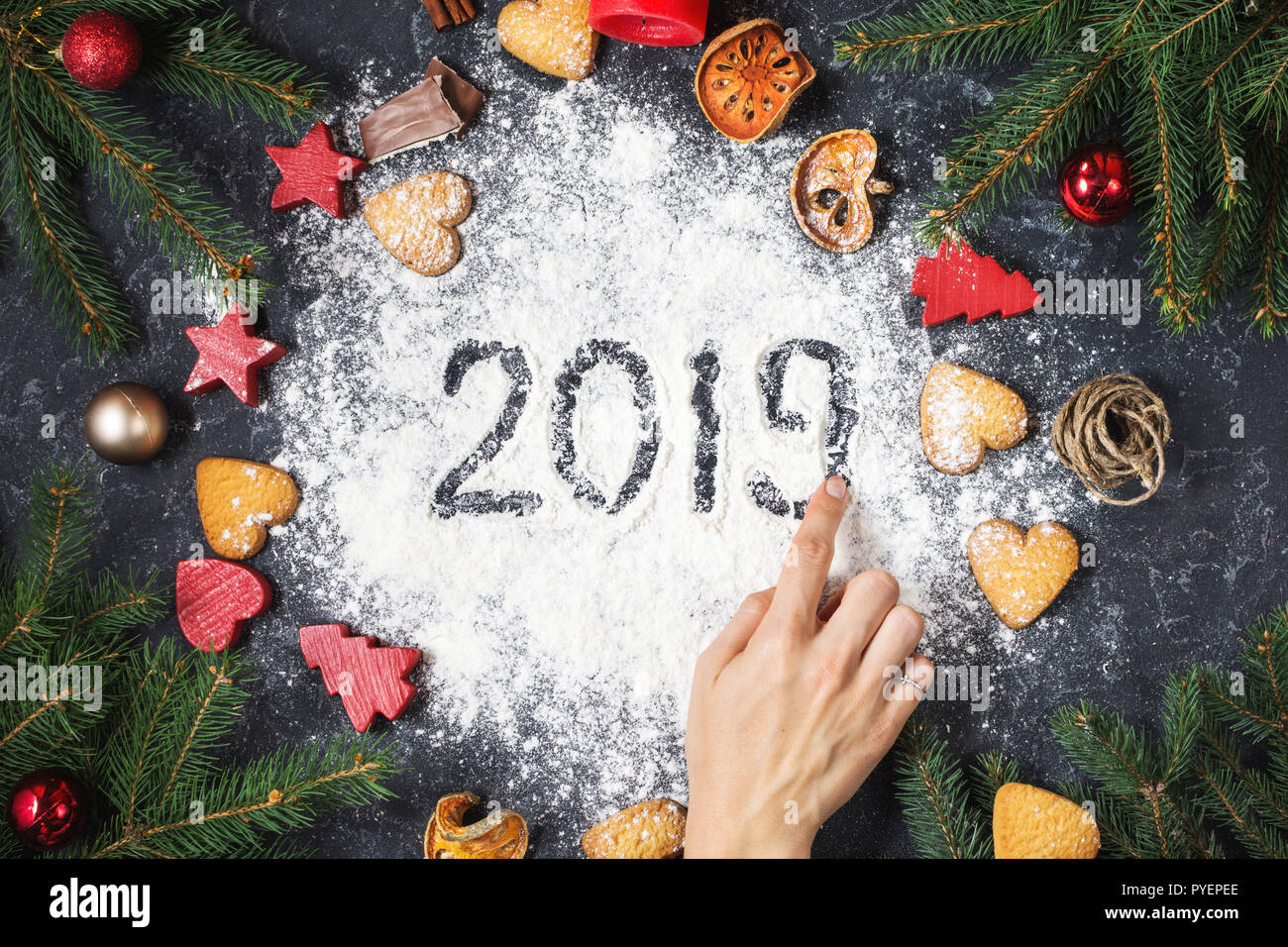 happy new year 2019 written on flour and christmas decorations gingerbread cookies on dark stone background new year greeting card