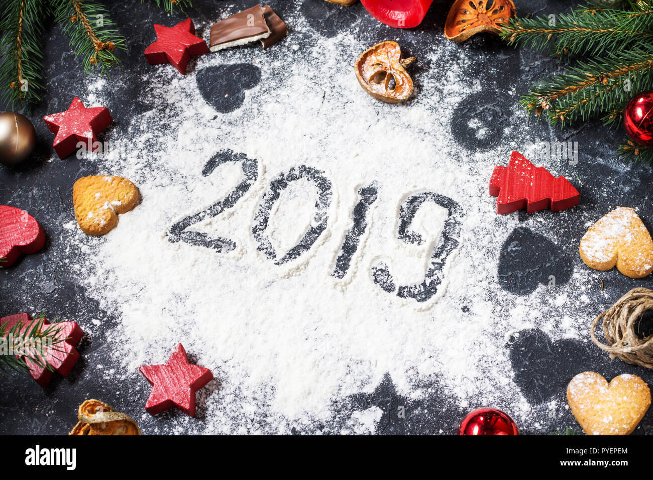 Happy New Year 2019 written on flour and Christmas Decorations Gingerbread cookies on dark stone background. New Year greeting card - Stock Image