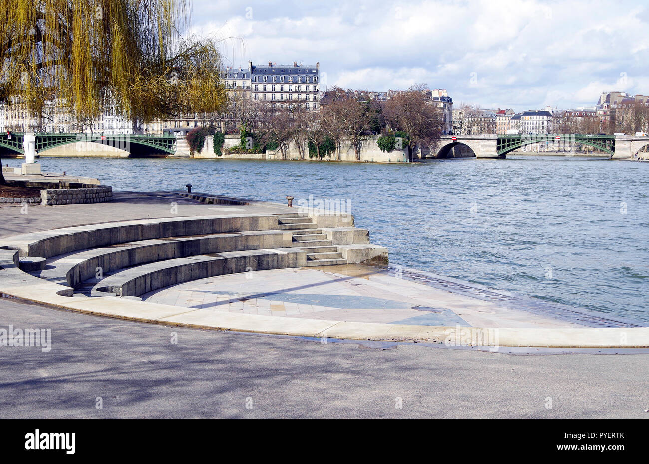 Paris, France, the western end of the Ile St Louis and the two parts of the Pont de Sully, with a stepped aedicule in the river bank in the foreground - Stock Image
