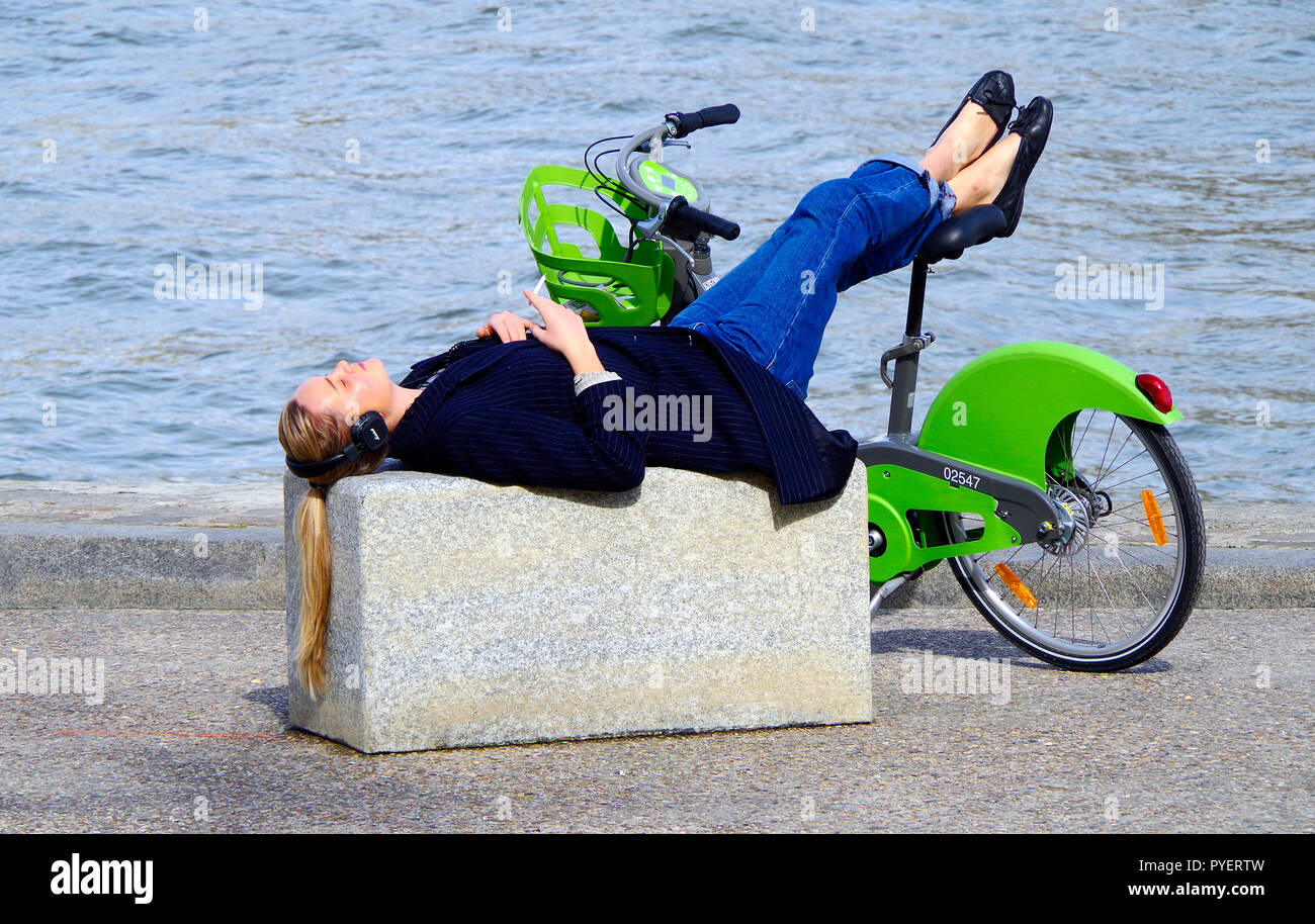 Young woman with long hair, pin-striped jacket and blue jeans, lying on a stone wall, beside the river Seine with feet resting on a velib rented bike - Stock Image