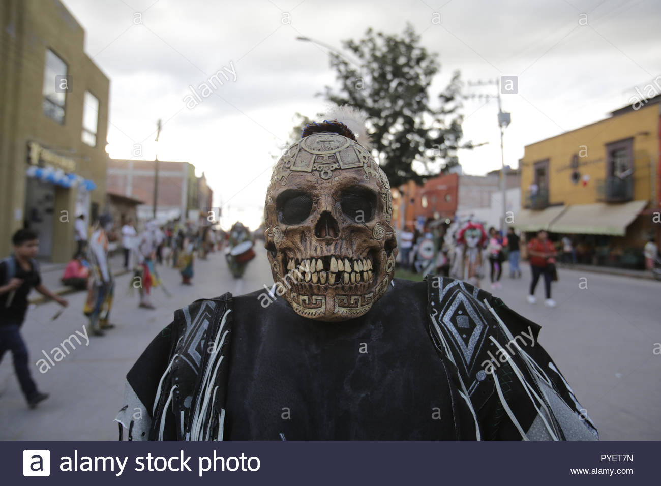 A dancer in a skull mask at an annual parade in mexico - Stock Image