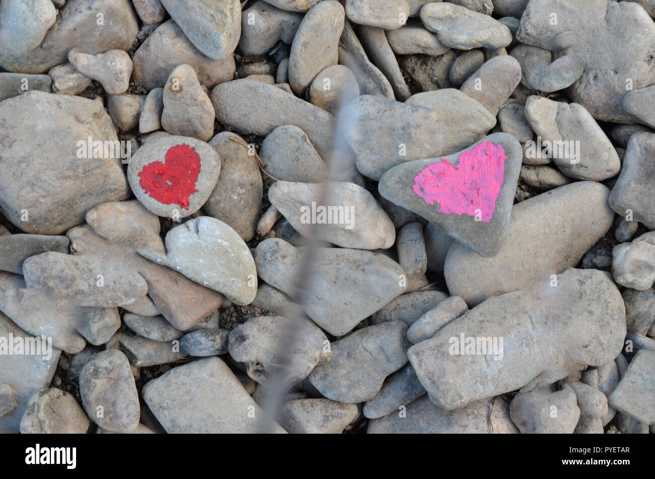 Cutting knife diving pink heart painted with lipstick on piece of stone. Symbol of the end of love and of two people break up and divorce - Stock Image