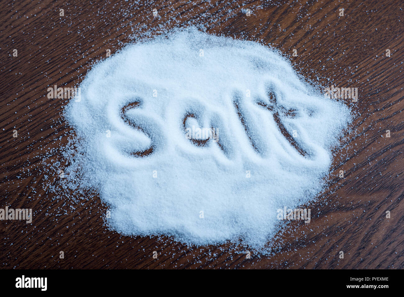 salt on wooden background, writing Stock Photo
