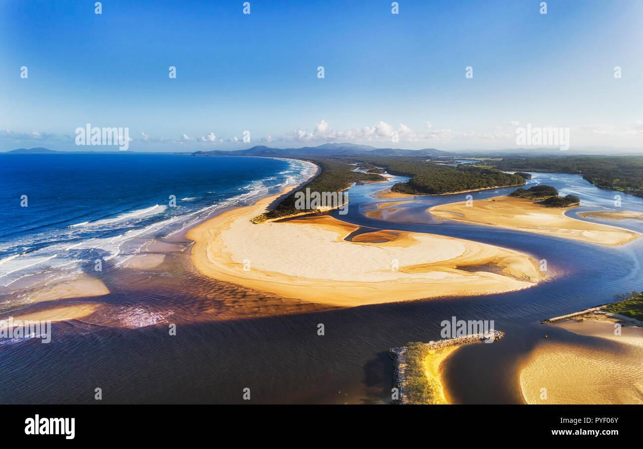 Flat sand dunes at delta of Nambucca river entering Pacific ocean through wide sandy beach of Australian coast around Nambucca heads town - aerial vie Stock Photo