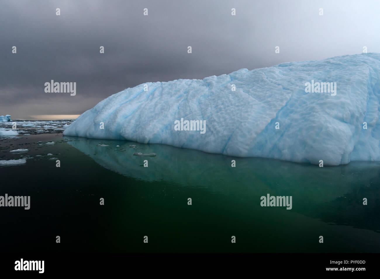 blue ice berg reflected in still water antarctic peninsula antarctica - Stock Image