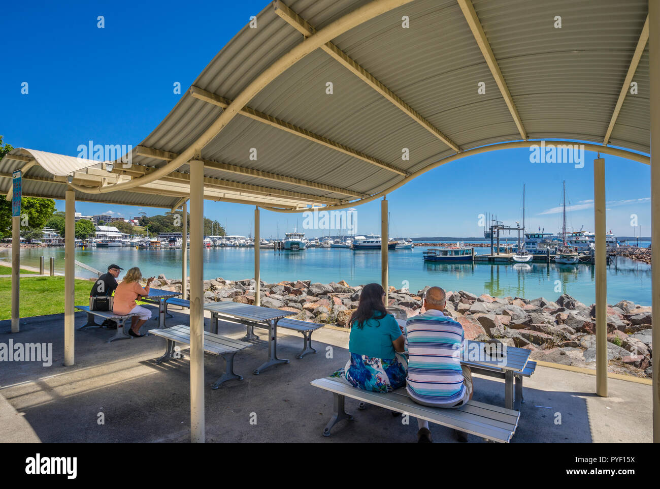picnic tables at Nelson Bay Foreshore Reserve with view of the marina and wharf, Port Stephens, Hunter Region, New South Wales, Australia - Stock Image