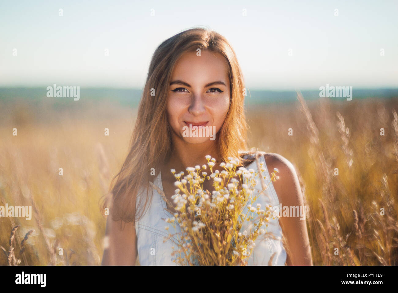 Attractive young woman standing smiling in the meadow in sleeveless jean sundress looking in camera - Stock Image
