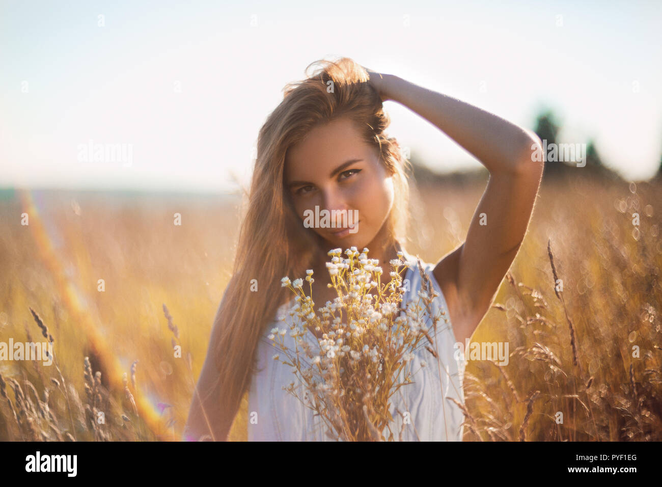 Attractive young woman standing in the meadow in sleeveless jean sundress handing her long hair - Stock Image