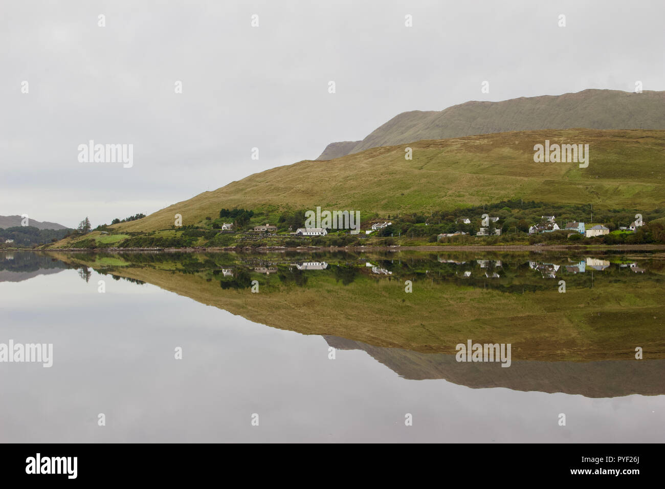 View of a still lake on an overcast day with reflection of the landscape of Connemara in the region of western Ireland - Stock Image
