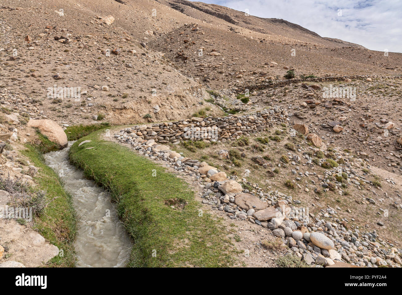 Typical traditional Central Asian water canal, or water dyke carrying water to villages, Langar, Tajik Wakhan, Pamir Mountains, Tajikistan - Stock Image
