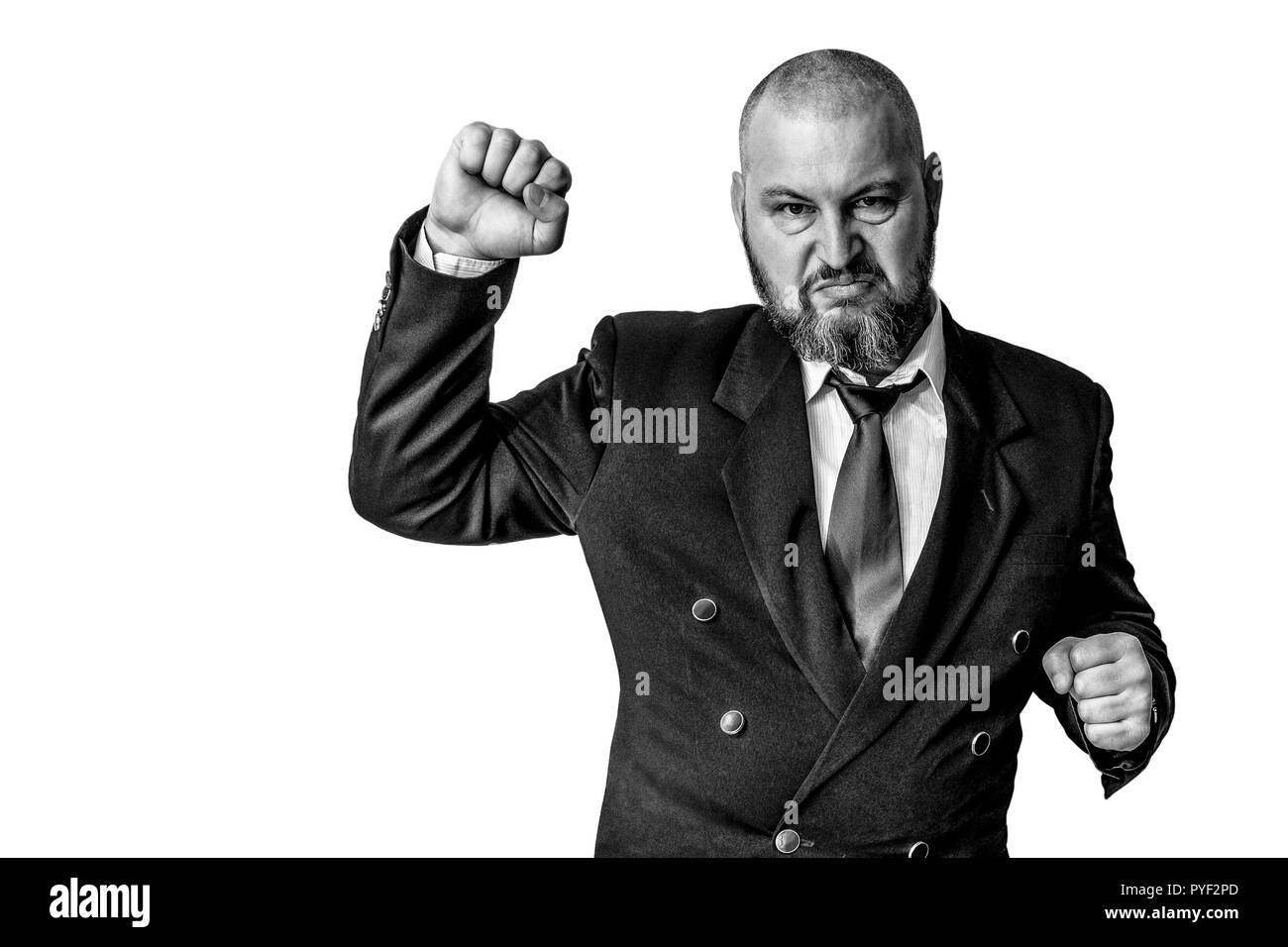 A man with a determined expression raised his hand in a clenched fist to the top. Monochrome photo. - Stock Image