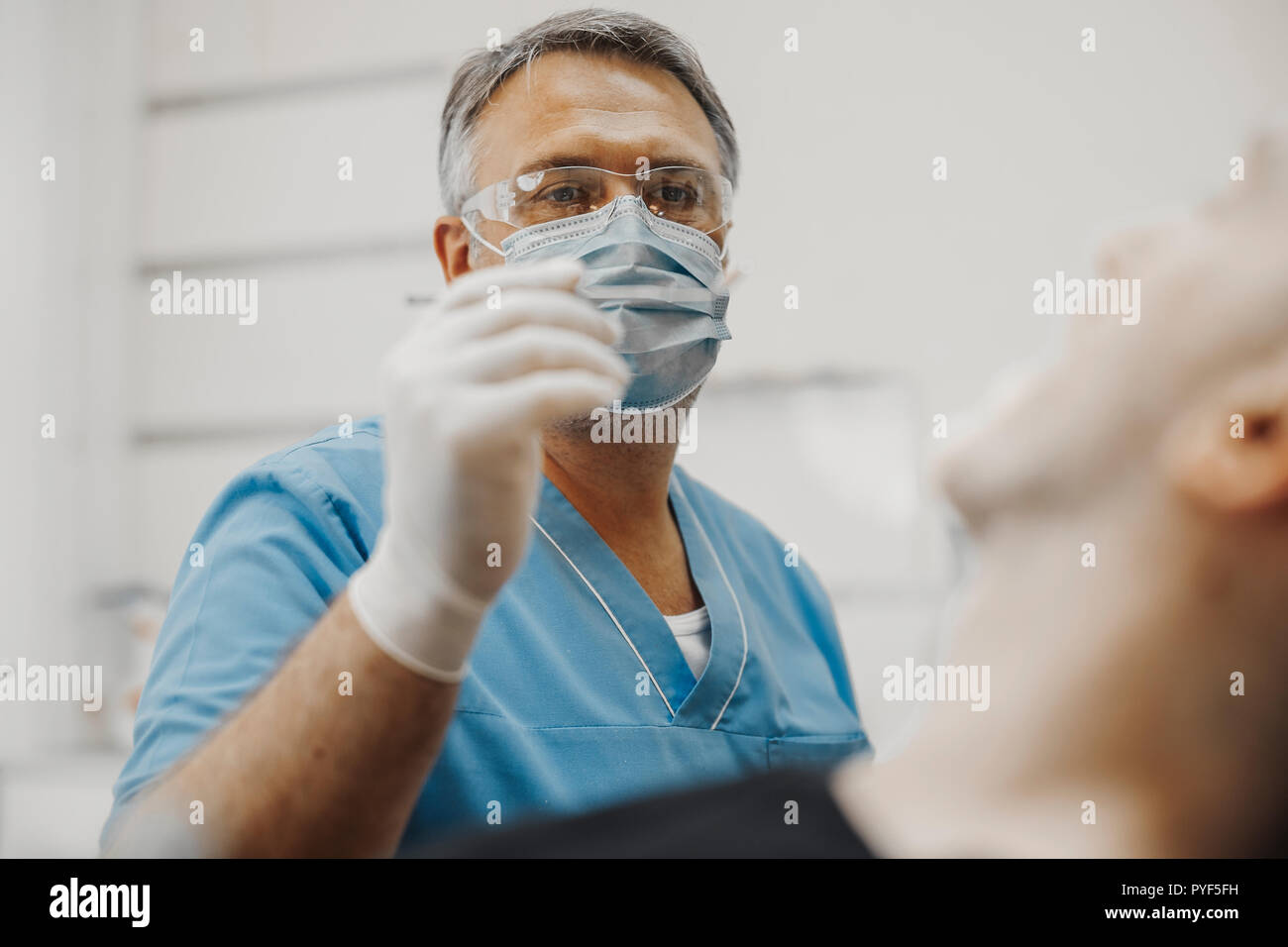 Close up of dentist in blue uniform checking up client teeth health condition. Stock Photo