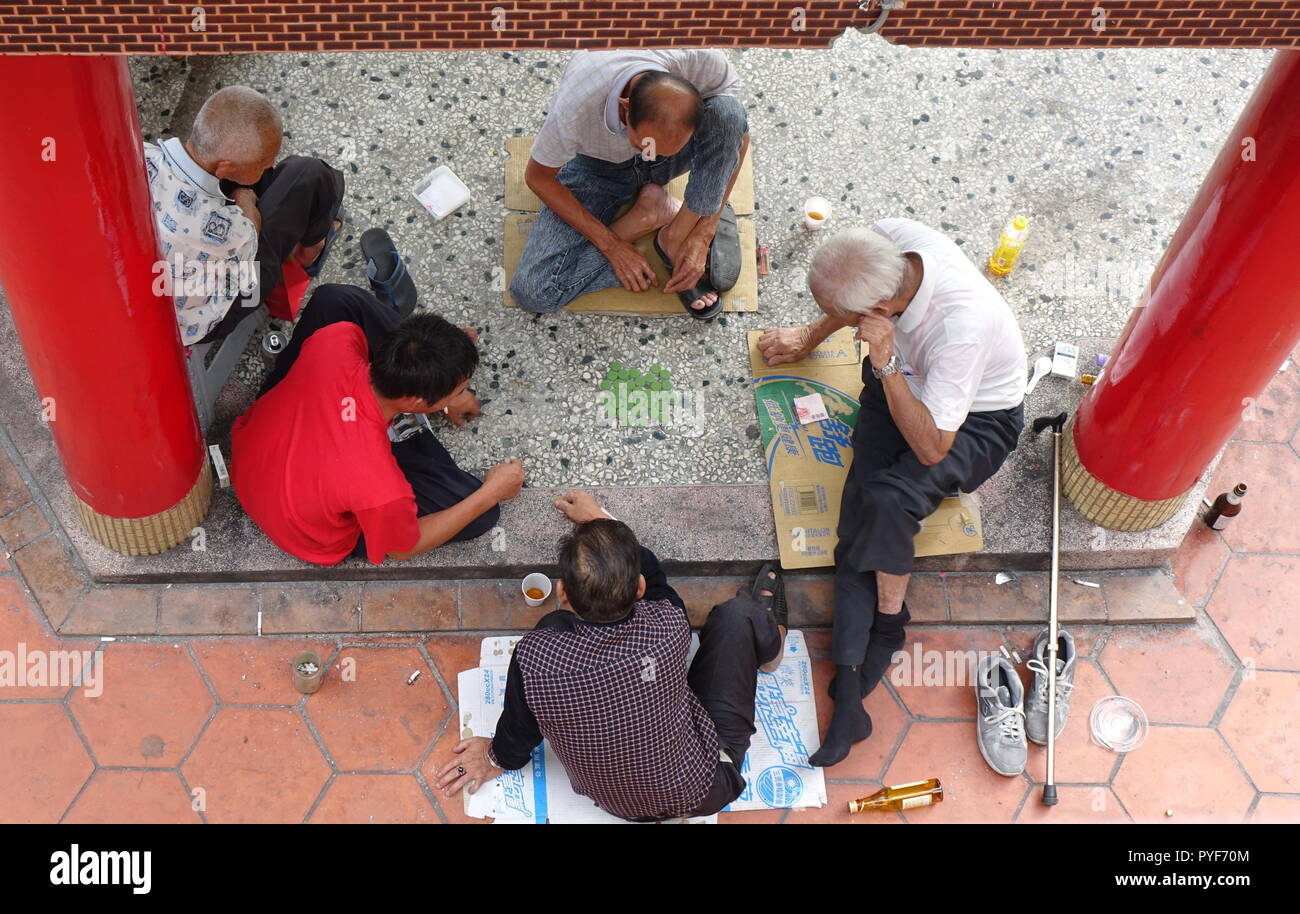 KAOHSIUNG, TAIWAN -- OCTOBER 19, 2018: Four elderly men play checkers under the roof of a local temple. Stock Photo
