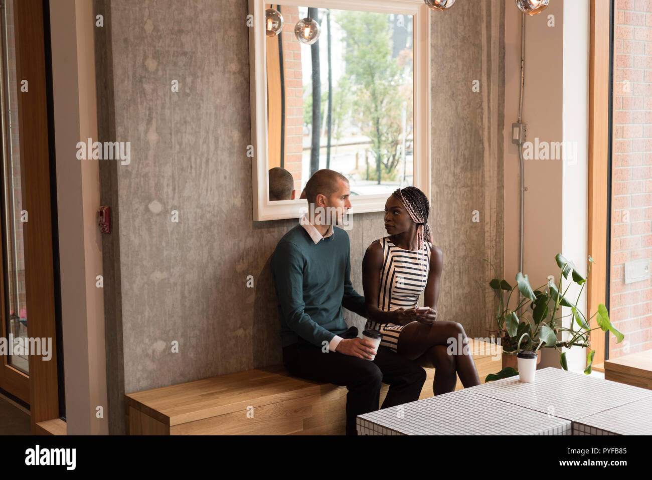 Couple interacting with each other in cafe Stock Photo