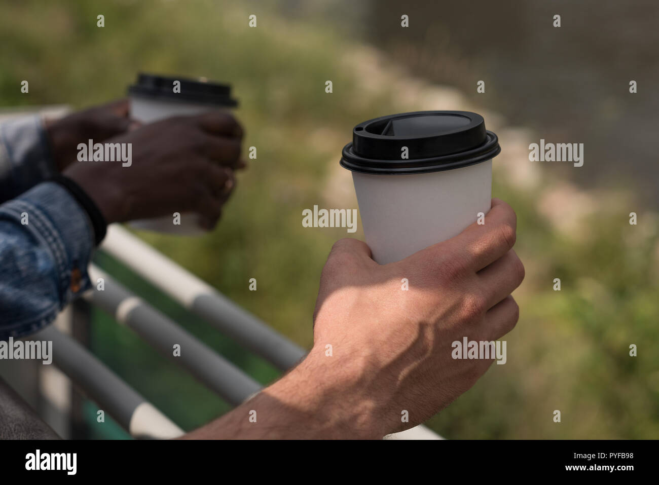 Couple with disposable cups leaning on the railings - Stock Image