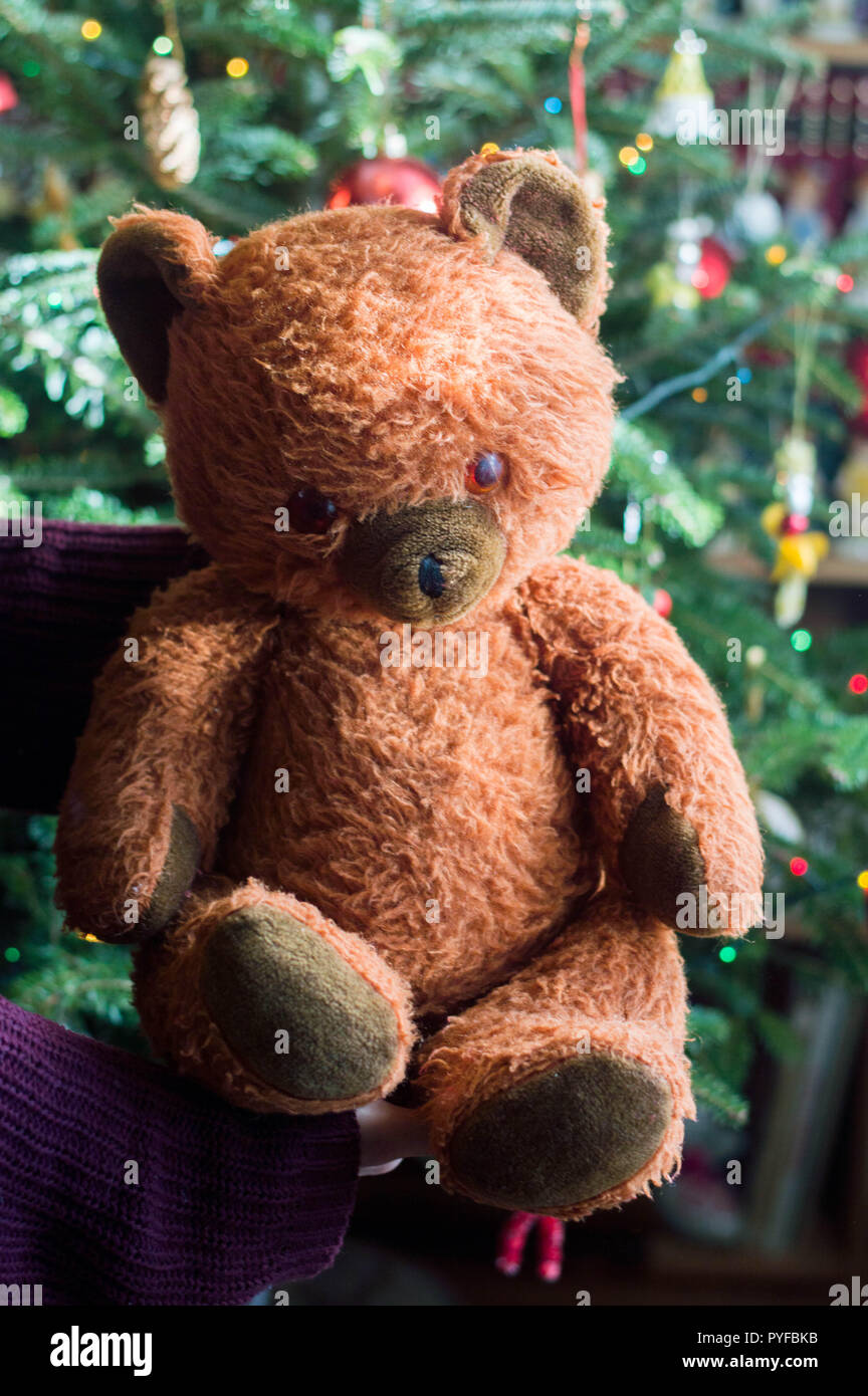 42ad3ad659 Child hold in hand a vintage stuffed teddy bear toy - its a christmas  present. In the background a decorated christmas tree with light garlands  and gl