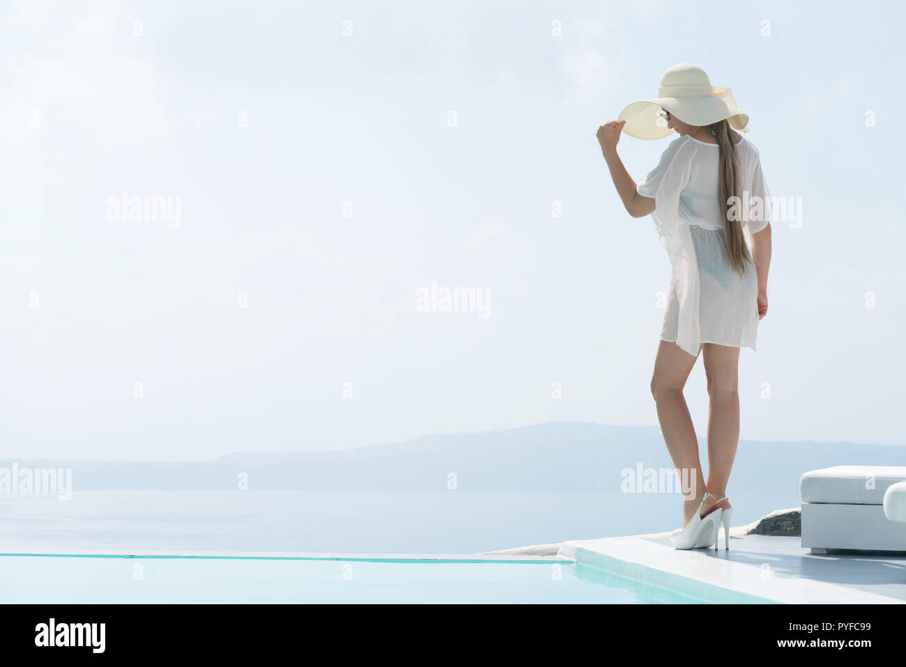 attractive girl in tunic and wide-brimmed hat posing near the pool. - Stock Image