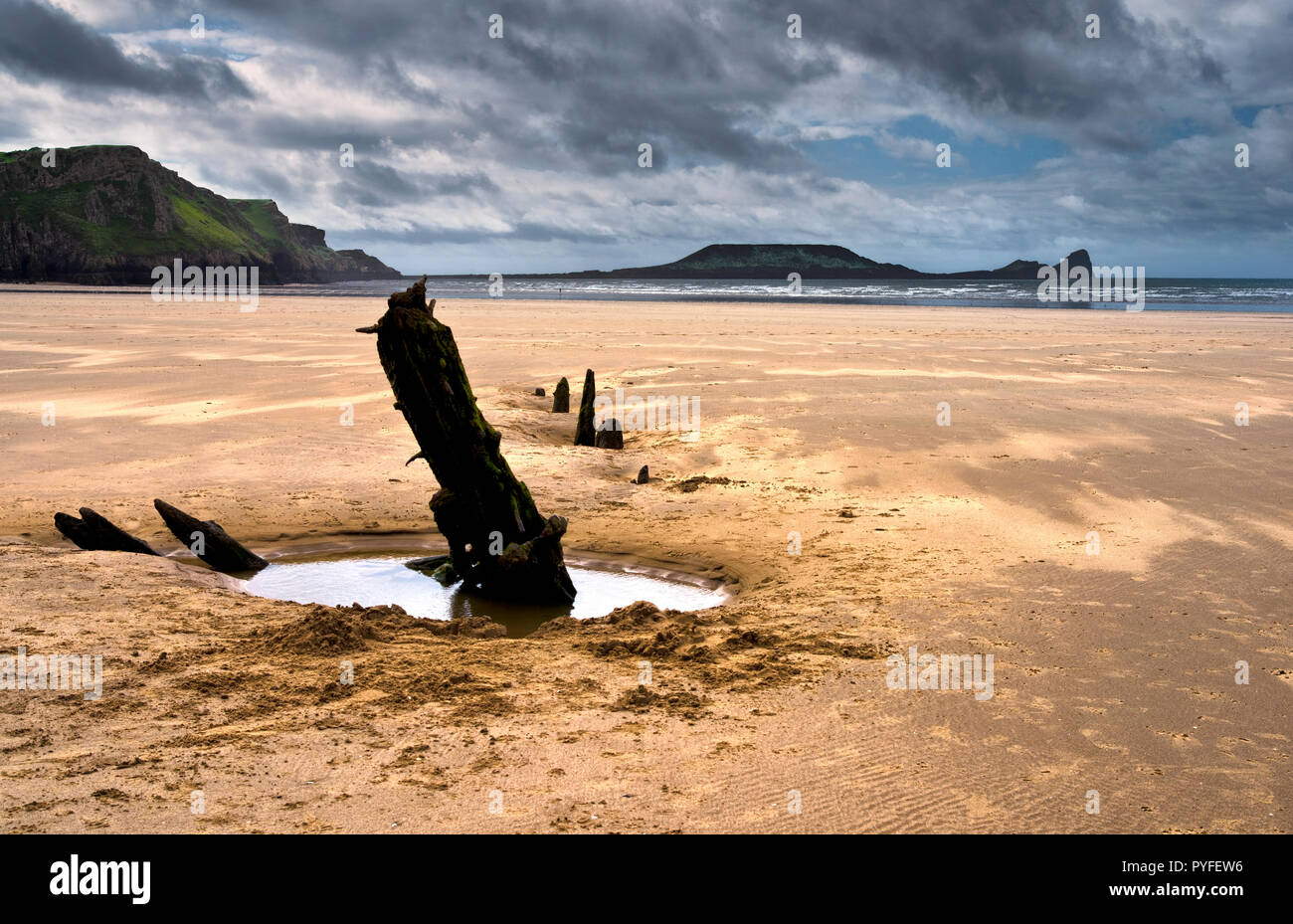 The wreck of the Helvetia and Worm's Head, Rhossili Bay, the Gower Peninsula, South Wales (1) - Stock Image