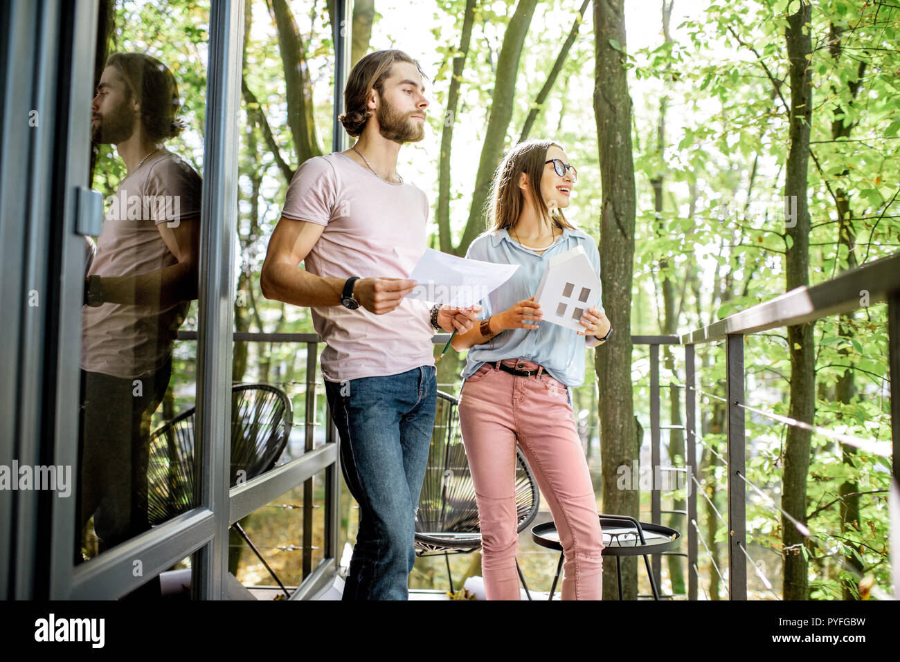 Young creative couple of architechts or designers working with house model and blueprints on the balcony of their office in the forest Stock Photo
