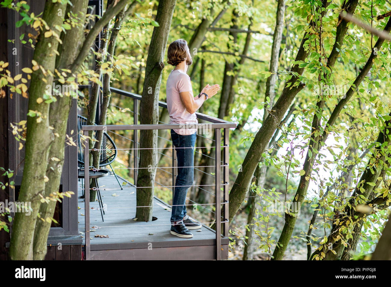 Portrait Of A Handsome Man On The Balcony Of The House In The Beautiful Forest Stock Photo Alamy