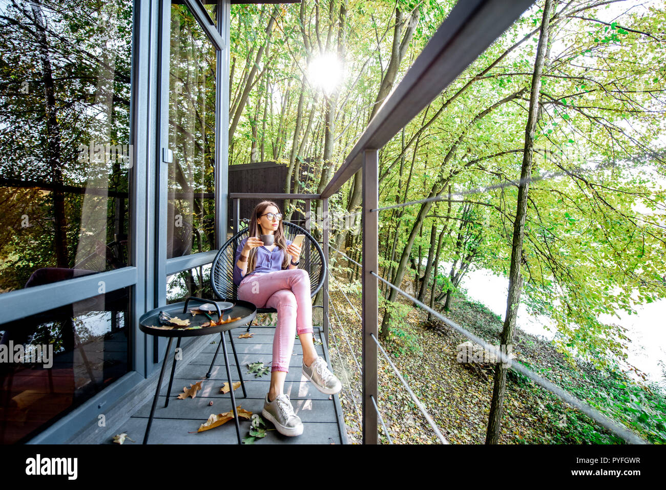 Young Woman Enjoying Nature Sitting With Coffee On The Balcony Of The House In The Beautiful Forest Stock Photo Alamy