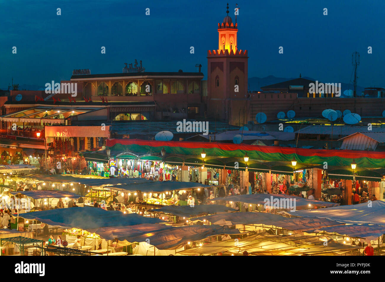 MOROCCO MARRAKECH JEMAA EL FNA THE SQUARE FOOD MARKET AT NIGHT WITH MOSQUE TOWER - Stock Image