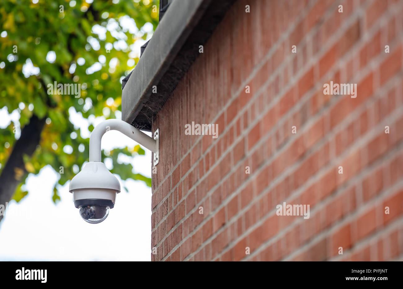 Security concept. Surveillance CCTV Camera on a brick wall, closeup view - Stock Image