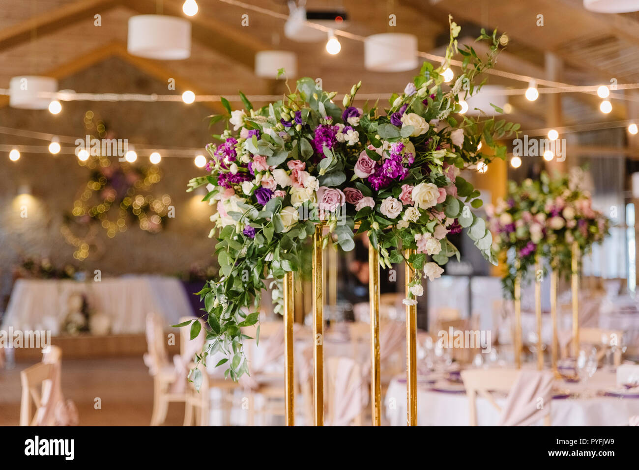 The high support in golden color decorated with flowers on a holiday table. - Stock Image