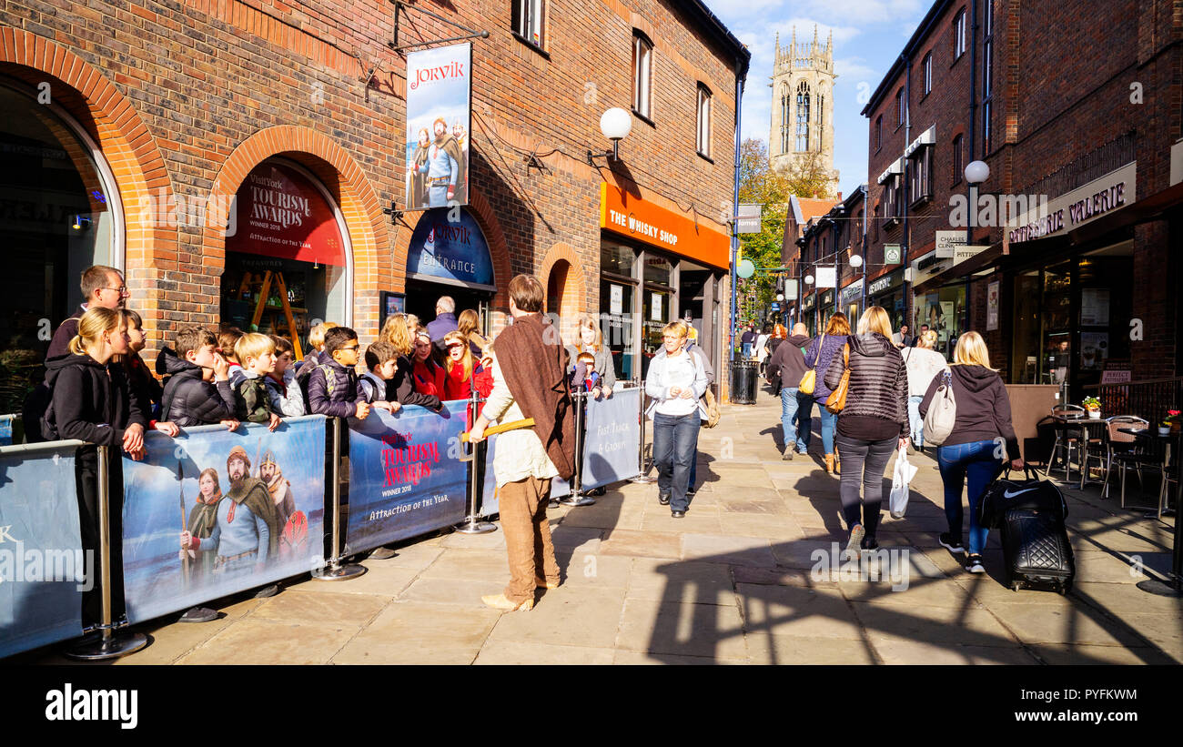 Children attending to a Guide while waiting for admission to the Jorvik Viking Centre, Coppergate, York, UK - Stock Image