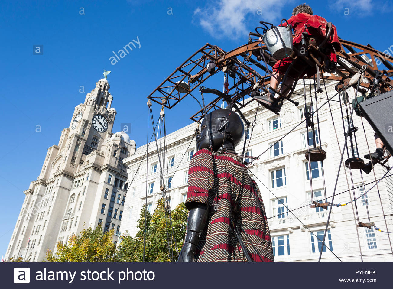 Little Boy Giant puppet and Royal de Luxe puppeteer walking past Cunard Building and Royal Liver Building, Liverpool, UK, Liverpool's Dream, 2018 - Stock Image
