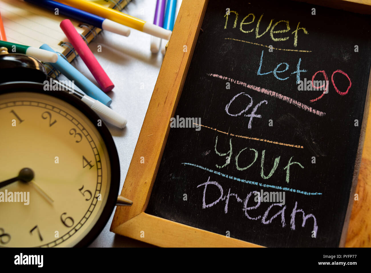 Never let go of your dream on phrase colorful handwritten on chalkboard, alarm clock with motivation and education concepts - Stock Image