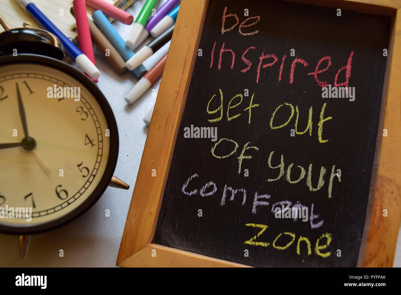 Be inspired get out of your comfort zone on phrase colorful handwritten on chalkboard, alarm clock with motivation and education concepts Stock Photo