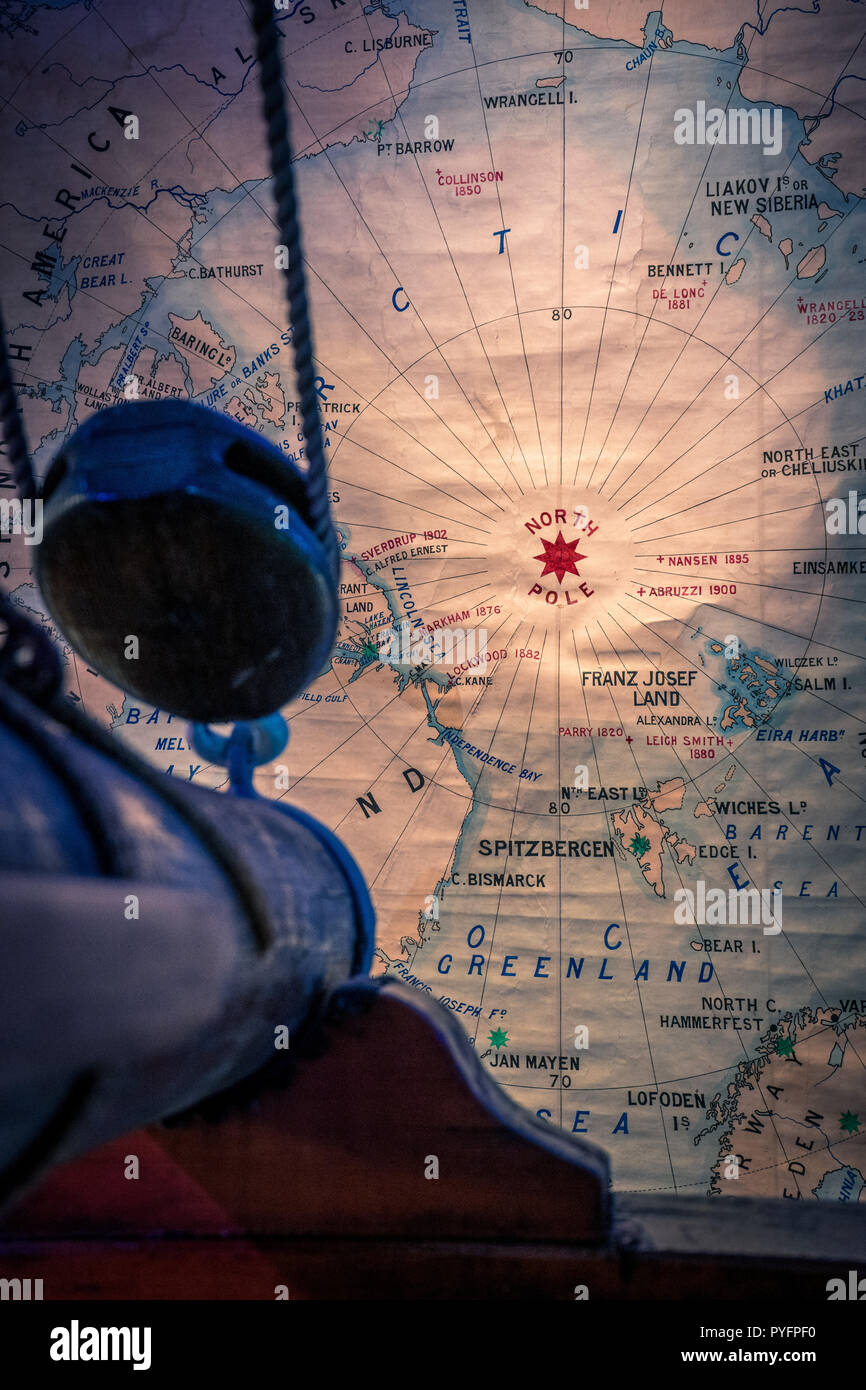 Ship for mast is pointing to the North Pole on the map as a concept of brave expeditions to the North pole - Stock Image
