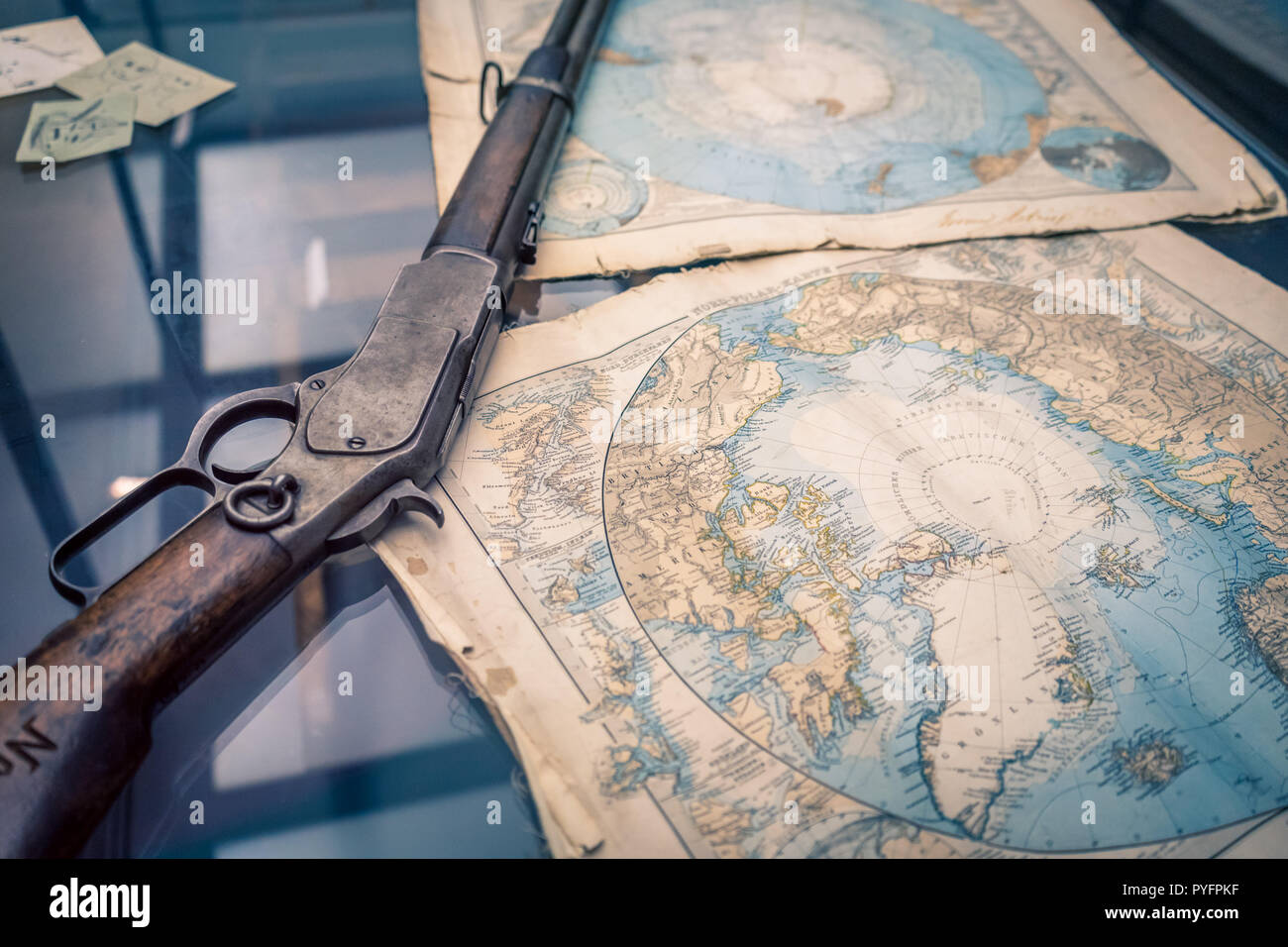 A vintage rifle and a vintage Antarctic region map as a concept of brave expeditions to the North pole Stock Photo