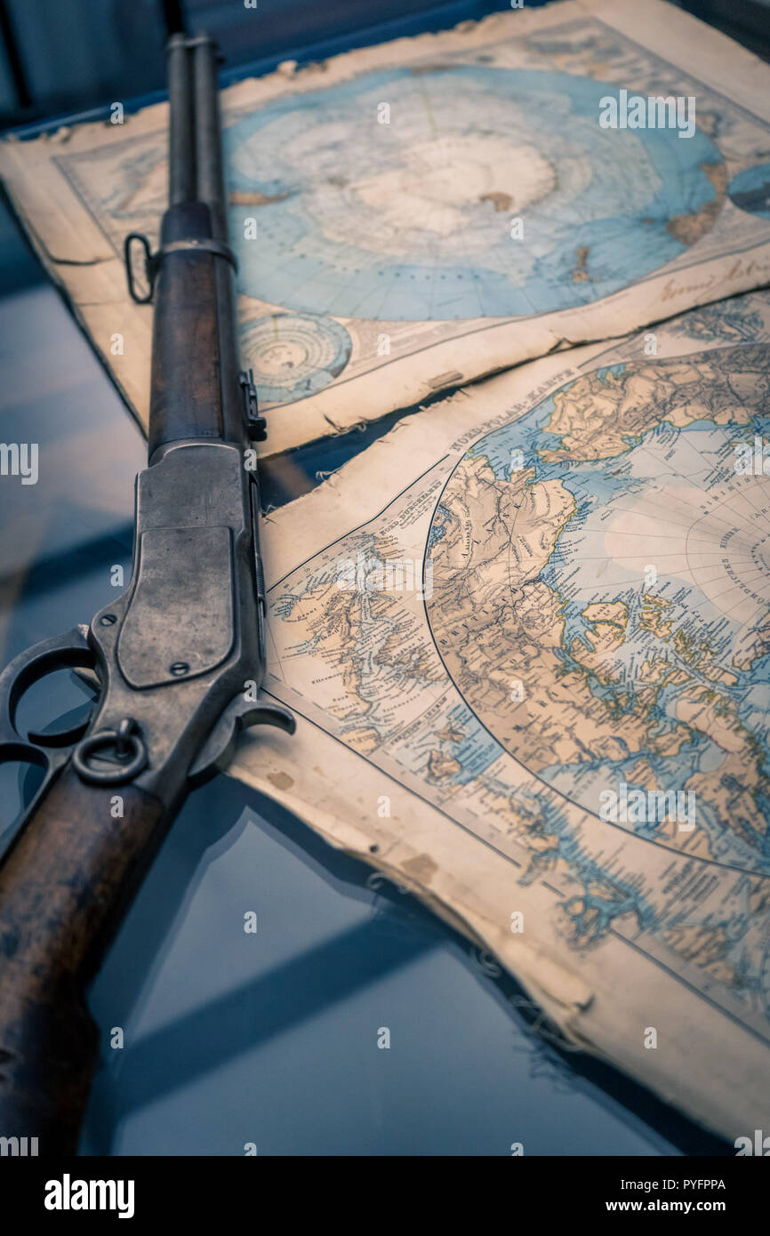 A vintage rifle and a vintage Antarctic region map as a concept of brave expeditions to the North pole - Stock Image