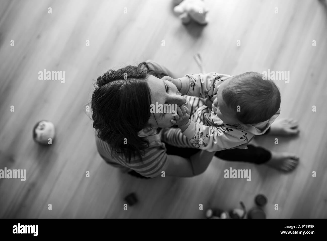 Top view of young mother sitting on living room floor lovingly playing with her baby daughter. Monochrome image. - Stock Image