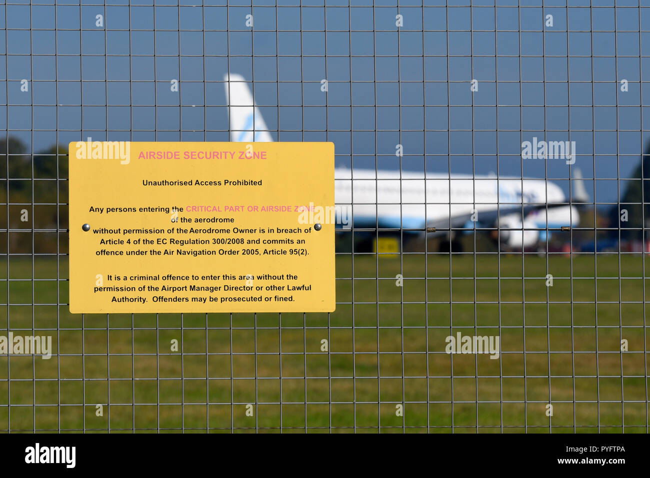 Airside security zone unauthorised access prohibited warning sign. Notice on perimeter fence with jet airliner plane taxiing past. Space for copy - Stock Image