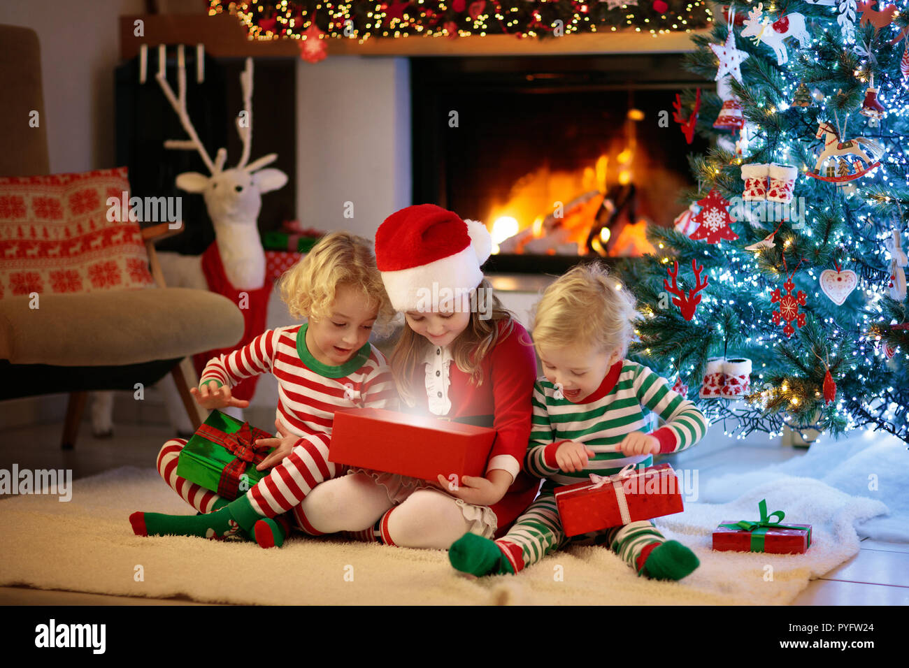 Children at Christmas tree and fireplace on Xmas eve. Family with ...