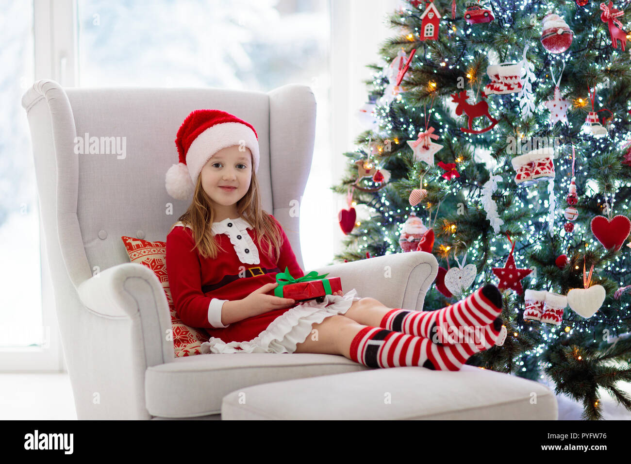 Child decorating Christmas tree and opening present and gift at home ...