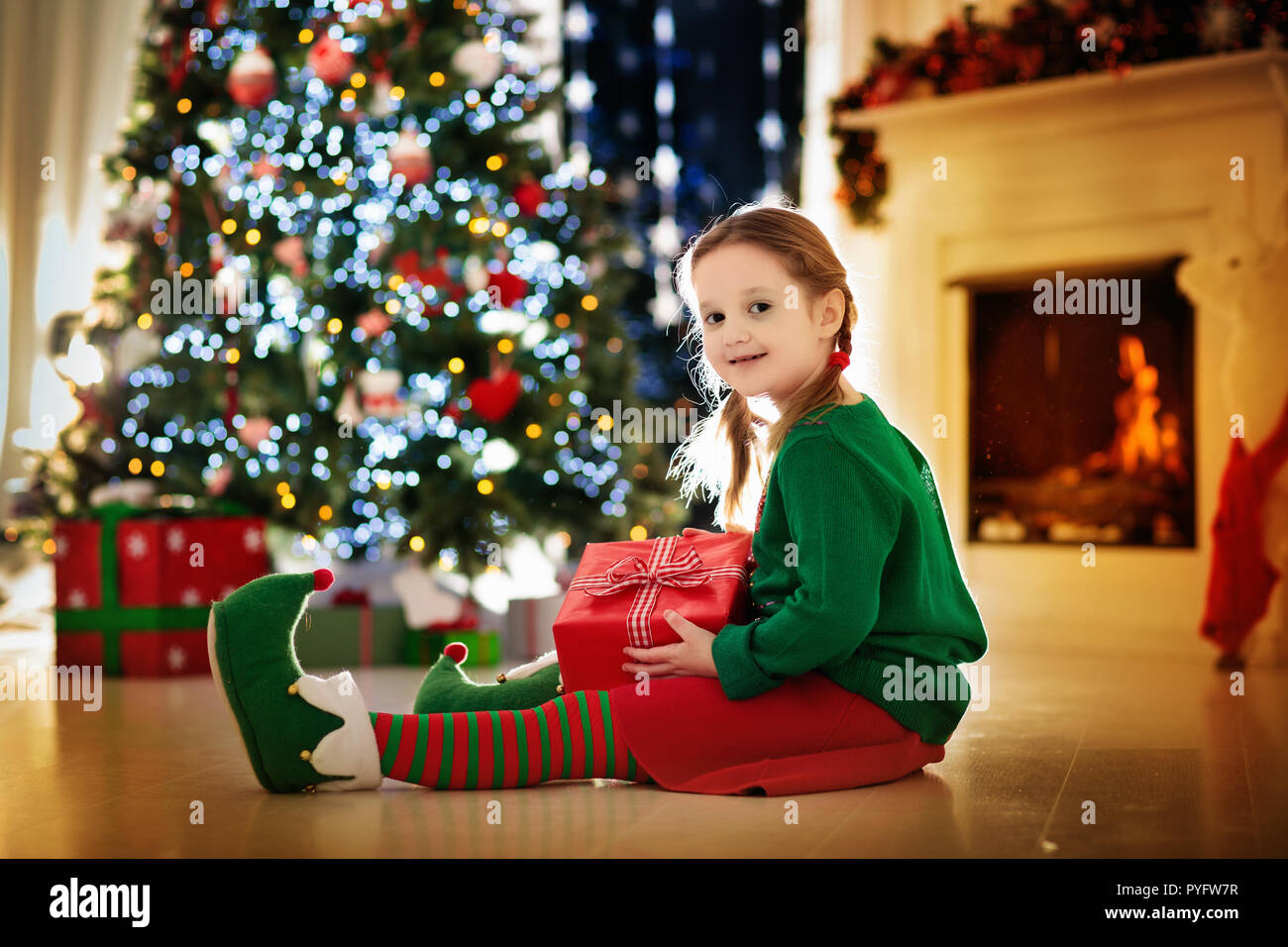 Child opening present at Christmas tree at home. Kid in elf costume ...