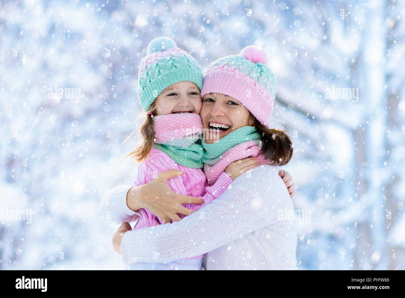 Mother and child in knitted winter hats play in snow on family Christmas  vacation. Handmade wool hat and scarf for mom and kid. Knitting for kids.  Kni 7831e6149644
