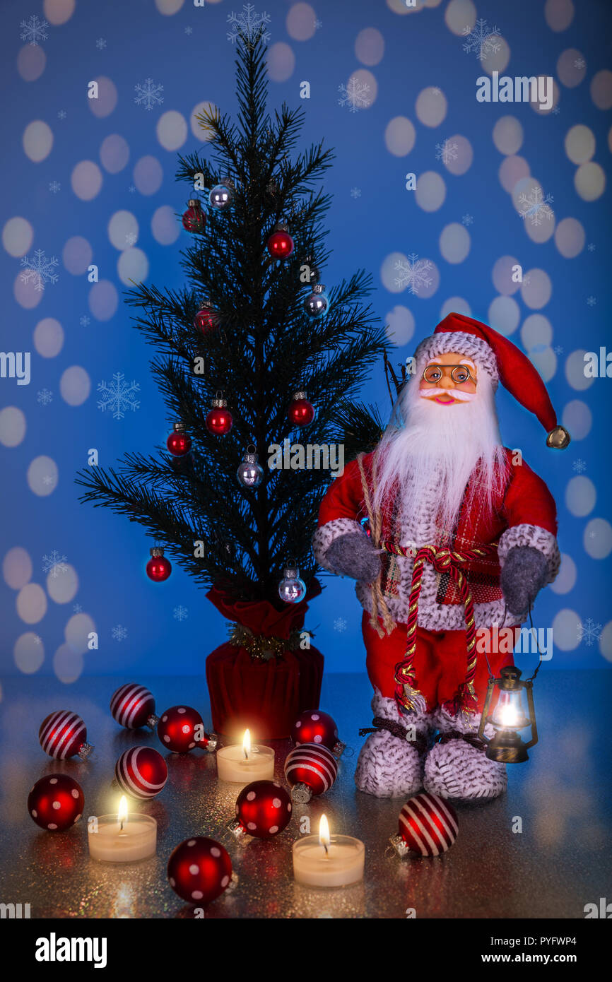 santa claus and christmas tree on a dark blue background with bokeh PYFWP4