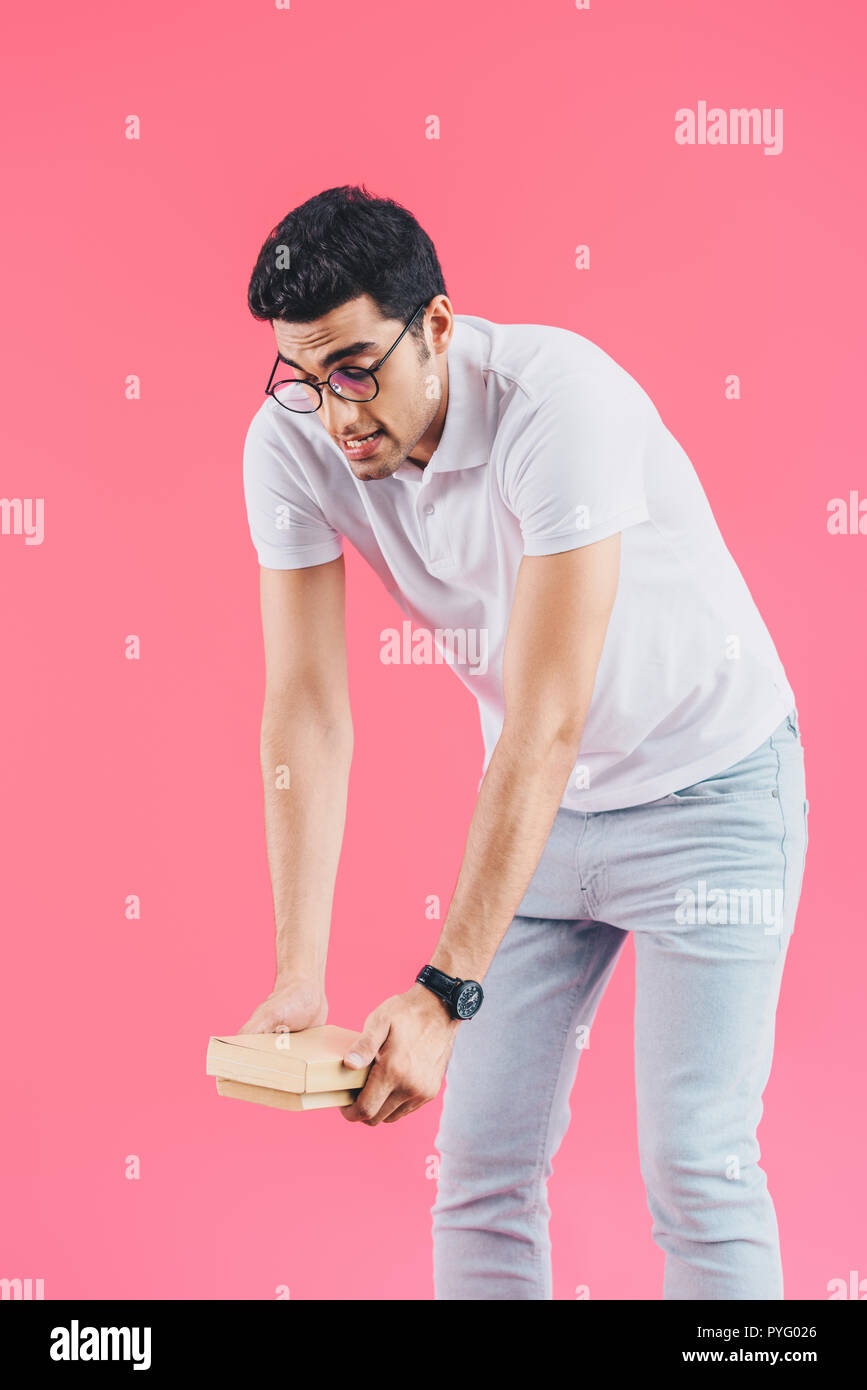 handsome grimacing student holding heavy books isolated on pink - Stock Image